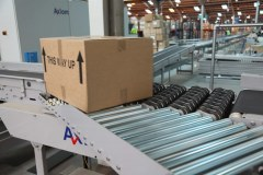 Roller conveyor merges parcel onto conveyor line