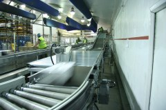 Belt conveyor on incline and roller conveyor transports parcels at high speeds